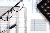 Business documents, eyeglasses and a calculator