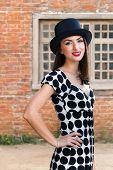 Happy young woman wearing top hat posing against vintage house o