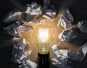 Light bulb with Crumpled paper on wood background