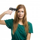 Portrait of a beautiful girl with pointing a gun on herself isolated on white background