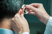picture of deaf  - Doctor inserting hearing aid in senior - JPG