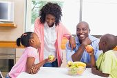 Happy family having fruit together at home in the kitchen