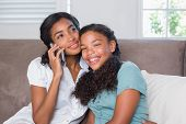 Happy mother and daughter using smartphone together on sofaat home in living room
