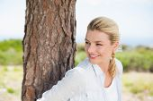 Attractive happy blonde standing by tree on a sunny day