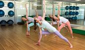 Yoga class in extended triangle pose in fitness studio at the leisure center