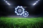 Cloud in shape of cogs and wheels against football pitch with bright lights