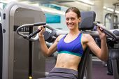 Fit smiling brunette using weights machine for arms at the gym