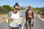Hiking couple looking at map on the road on a sunny day