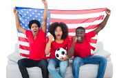 Cheering football fans in red sitting on couch with usa flag on white background
