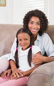 Pretty mother sitting on the couch with her daughter smiling at camera at home in the living room