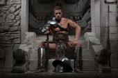 Gladiator in armour sitting on steps of ancient temple with helm