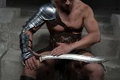 stock photo of sparta  - Closeup portrait of gladiator in armour sitting on steps of ancient temple looking at sword. Concept of masculine power, strength