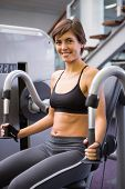 Smiling brunette using weights machine for arms at the gym