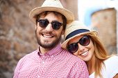 Happy girl and her boyfriend in hats and sunglasses looking at camera