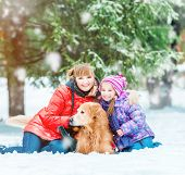 mum with a daughter and their dog in winter park