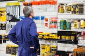 Rear view of worker with hands on hip standing in hardware store