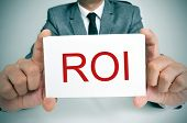 businessman sitting in a desk showing a signboard with the text ROI, ROI, acronym for Rate of Intere
