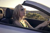 beautiful woman who is driving a wonderful car at the sunset