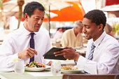 Two Businessmen Having Meeting In Outdoor Restaurant