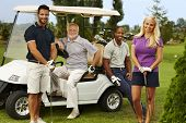 Happy team of golfers ready to play, standing and sitting around golf cart, smiling, looking at came