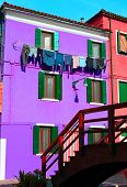 Colored House On The Island Of Burano With Clothes Hung Out To Dry
