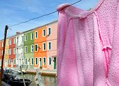 Pink Cotton Bathrobe Laid Out To Dry And The Colorful Houses