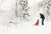 man and golden retriever in the snow