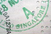 stock photo of fragmentation  - Singapore immigration stamp closeup fragment with selective focus - JPG