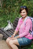 Young Brunette Woman And Ring-tailed Lemur Sitting On The Bench