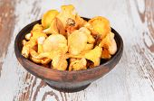 foto of chanterelle mushroom  - Chanterelle mushroom in clay bowl on wooden background - JPG