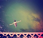 image of trestle bridge  -  a boy jumping of an old train trestle bridge into a river toned with a retro vintage instagram filter effect   - JPG
