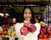 Young Woman Smiling With Red Apples At Market Store
