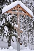 Orthodox antique handmade wooden cross in winter forest