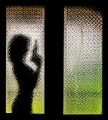 stock photo of tragic  - Silhouette of Woman with Gun Behind Glass Door - JPG