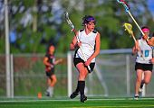 Girls Varsity Lacrosse player moving in for a shot