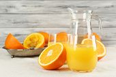 Glass of orange juice with slices on metal tray on table and color wooden wall background
