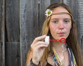 Young beautiful hippies girl blowing bubbles outdoors.