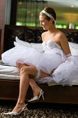 picture of underskirt  - Boudoir attractive young woman wearing lingerie and underskirt and she sits on the bed - JPG