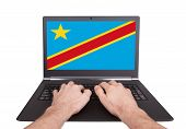 picture of congas  - Hands working on laptop showing on the screen the flag of Conga - JPG