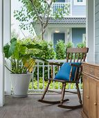 stock photo of planters  - wooden rocking chair on front porch with pillow and planter - JPG