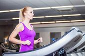 Attractive young woman running on a treadmill exercise at the fitness club