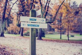 picture of opposites  - Signpost in a park or forested area with arrows pointing two opposite directions towards Men and Women - JPG
