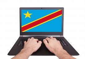 pic of congas  - Hands working on laptop showing on the screen the flag of Conga - JPG