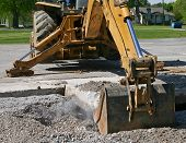 image of backhoe  - dust flies as a backhoe bucket lifts a slab of concrete from the roadway - JPG
