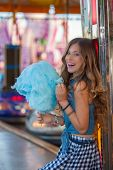 stock photo of candy cotton  - teen girl at carnival or fair with candy floss or cotton candy   - JPG