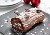 stock photo of yule  - Yule log cake decorated with chocolate leaves on a Christmas table - JPG