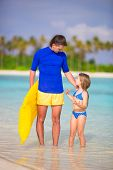 stock photo of mattress  - Little girl and young father with air mattress on beach vacation - JPG