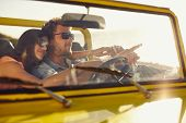 foto of road trip  - Young man driving car pointing something interesting to his girlfriend - JPG