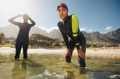 image of triathlon  - Confident young woman in wet suit standing in water looking at camera - JPG