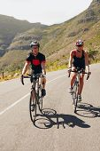 foto of triathlon  - Couple of cyclists riding bicycles on a country road - JPG